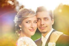Pares jovenes de la boda en prado del verano imagenes de archivo