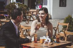 Pares jovenes de la boda en su día que se casa, relajándose en una barra y comiendo una cerveza fotografía de archivo libre de regalías
