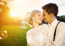 Pares jovenes de la boda en un prado del verano foto de archivo