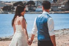 Pares jovenes de la boda que caminan en la playa imagenes de archivo