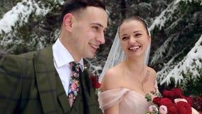 Pares jovenes de la boda que caminan, sonriendo y hablando llevando a cabo las manos en bosque nevoso durante las nevadas Boda de almacen de video