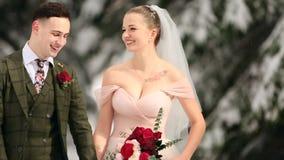 Pares jovenes de la boda que caminan, sonriendo y hablando llevando a cabo las manos en bosque nevoso durante las nevadas Boda de