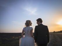Pares jovenes de la boda que hablan en el campo en la puesta del sol Fotos de archivo