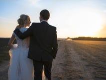 Pares jovenes de la boda que hablan en el campo en la puesta del sol Imágenes de archivo libres de regalías
