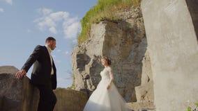 Pares jovenes de la boda que presentan en las escaleras de piedra viejas Castillo antiguo arruinado 4k almacen de metraje de vídeo