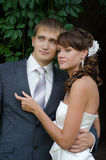 Pares jovenes de la boda que presentan en su día de boda Foto de archivo libre de regalías
