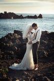 Pares jovenes de la boda sobre el océano Fotos de archivo libres de regalías