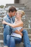 Pares jovenes de la cadera que se sientan en los pasos que muestran el afecto Foto de archivo