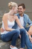 Pares jovenes de la cadera que se sientan en los pasos que sonríen en uno a Imagen de archivo libre de regalías