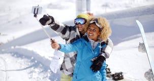 Pares jovenes de la diversión que presentan en la nieve para un selfie imagenes de archivo