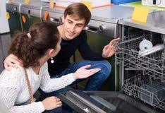 Pares jovenes de la familia que eligen la nueva lavadora del plato en superm Fotos de archivo