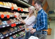 Pares jovenes de la familia que eligen las salchichas enfriadas en tienda Imagen de archivo libre de regalías