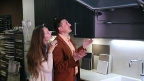 Pares jovenes de la familia que miran la cocina moderna en tienda almacen de video