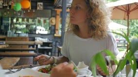 Pares jovenes de la forma de vida sana que comen la ensalada verde fresca en restaurante vegetariano HD a cámara lenta Phangan, T almacen de metraje de vídeo