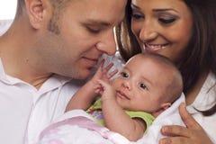 Pares jovenes de la raza mixta con el bebé recién nacido Fotografía de archivo