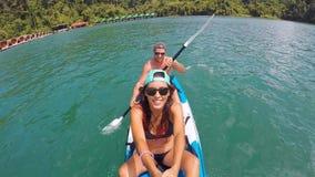 Pares jovenes de la raza mixta kayaking en el lago Selfie activo a cámara lenta del gopro de la forma de vida de HD almacen de video