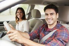 Pares jovenes de la raza mixta que conducen en el coche el día de fiesta, retrato fotos de archivo