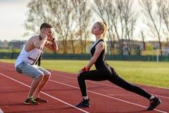 Pares jovenes de la salud que hacen estirando el ejercicio que se relaja Foto de archivo