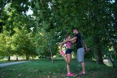 Pares jovenes de la salud que hacen estirando la relajación y el calentamiento del ejercicio después de activar y de correr en pa Fotografía de archivo