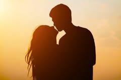Pares jovenes de la silueta que se besan sobre fondo de la puesta del sol Foto de archivo libre de regalías