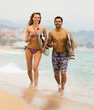 Pares jovenes de las personas que practica surf en la playa Imagen de archivo libre de regalías