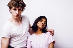 Pares jovenes de las razas mixtas novia y novio que se divierten en el fondo blanco, concepto adolescente de la gente de la forma Fotos de archivo libres de regalías