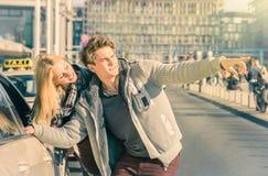 Pares jovenes de los amantes que tratan de un taxi en Berlin City Fotos de archivo libres de regalías