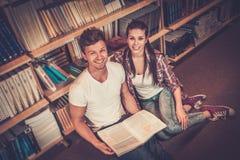 Pares jovenes de los estudiantes alegres que se sientan en el piso y que estudian en la biblioteca de universidad Foto de archivo libre de regalías