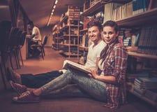 Pares jovenes de los estudiantes alegres que se sientan en el piso y que estudian en la biblioteca de universidad Imagen de archivo libre de regalías