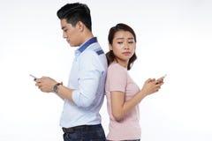 pares jovenes de los estudiantes con la tableta y el teléfono elegante Fotos de archivo