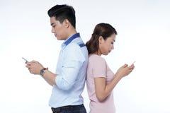 pares jovenes de los estudiantes con la tableta y el teléfono elegante Fotos de archivo libres de regalías