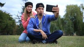 Pares jovenes de los estudiantes que hacen el selfie en la tableta almacen de video