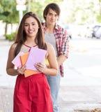 Pares jovenes de los estudiantes que sostienen los libros Fotos de archivo