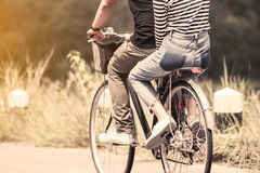 Pares jovenes de los inconformistas que montan una bicicleta junto foto de archivo