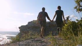 Pares jovenes de los turistas que vienen al top de la montaña almacen de metraje de vídeo