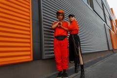 Pares jovenes de moda con los casquillos en elegante anaranjado brillante imágenes de archivo libres de regalías