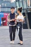 Pares jovenes de moda en área de compras, Pekín, China Fotos de archivo