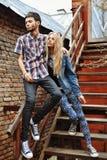 Pares jovenes de moda que se colocan en las escaleras y que abrazan cada uno más allá del horizonte Imagen de archivo libre de regalías