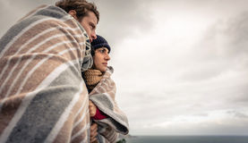 Pares jovenes debajo de la manta que mira el mar en a Imagen de archivo