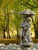 Pares jovenes debajo de un paraguas en el parque Imágenes de archivo libres de regalías