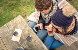 Pares jovenes debajo del smartphone de mirada combinado y Imagenes de archivo