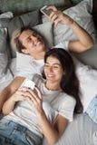 Pares jovenes del adicto al artilugio que se divierten con smartphones en cama Fotos de archivo