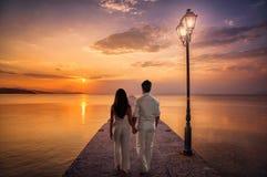 Pares jovenes del amor antes de la puesta del sol fotografía de archivo