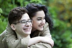 Pares jovenes del amor en el parque Muchacha que abraza el individuo y la mirada Imagenes de archivo