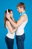 Pares jovenes del amor. Muchacho que introduce en los auriculares, música que escucha Foto de archivo libre de regalías