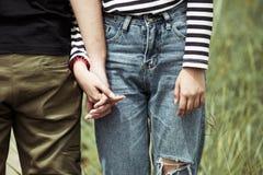 Pares jovenes del amor que llevan a cabo las manos juntas Fotografía de archivo libre de regalías