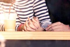 Pares jovenes del amor que llevan a cabo las manos juntas en el café Imagenes de archivo