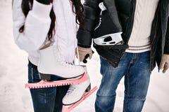 Pares jovenes del amor que sostienen sus patines en el hombro Días de fiesta de invierno imagenes de archivo