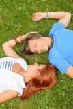 Pares jovenes del amor romántico que mienten en hierba Foto de archivo