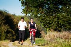 Pares jovenes del deporte que activan y que completan un ciclo Foto de archivo libre de regalías